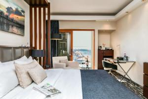 A bed or beds in a room at Carlton Tel Aviv Hotel – Luxury on the Beach