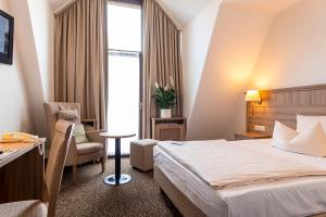 A bed or beds in a room at AMBER HOTEL Bavaria