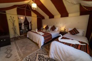 Een bed of bedden in een kamer bij Sahara Desert Luxury Camp