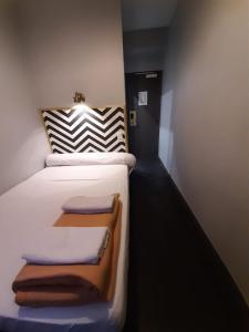 A bed or beds in a room at Hipotel Paris Belleville Gare de l'Est