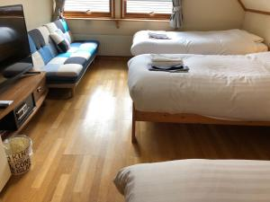 A bed or beds in a room at Rusutsu Lodges Pension Lilla Huset