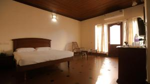 A bed or beds in a room at Kairali Heritage Resort