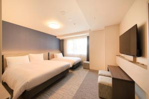 A bed or beds in a room at Richmond Hotel Yokohama Ekimae
