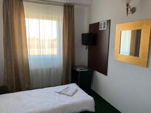 A bed or beds in a room at Arta Hotel