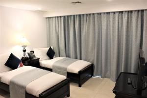A bed or beds in a room at Mövenpick Hotel & Resort Al Bida'a