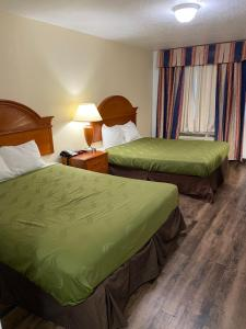 A bed or beds in a room at Desert Sands Inn & Suites