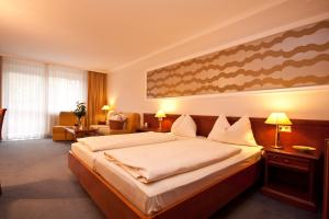 A bed or beds in a room at Vitalhotel der Parktherme