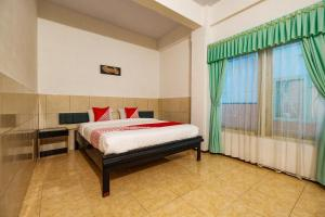 A bed or beds in a room at OYO 2855 Sartika Hotel Pati