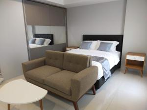 A bed or beds in a room at Deluxe Suite Apartel Azalea Suites Cikarang By Urban Style Collections A1819