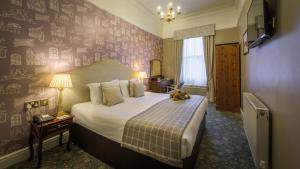 A bed or beds in a room at Old Hall Hotel