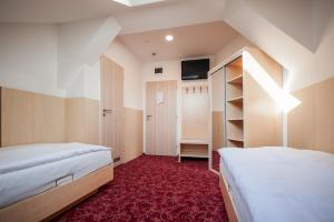 A bed or beds in a room at Hotel Pivovar
