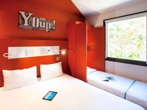 A bed or beds in a room at ibis budget Château-Thierry