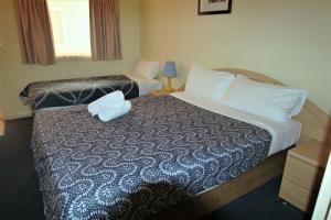 A bed or beds in a room at City East Motel