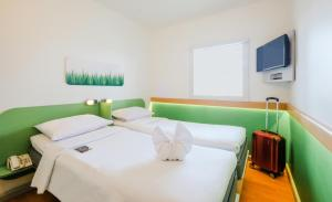 A bed or beds in a room at Ibis Budget Makassar Airport