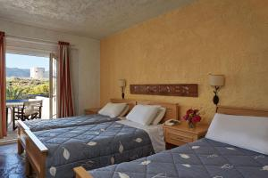 A bed or beds in a room at Andros Holiday Hotel