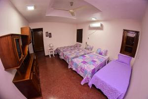 A bed or beds in a room at Palmera Hostel CDE