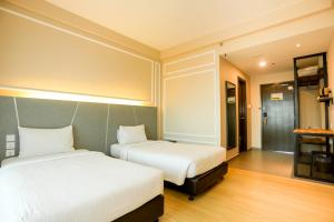 A bed or beds in a room at Marvelux Hotel