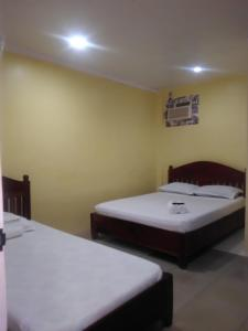 A bed or beds in a room at El Moro Beach Resort