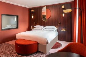 A bed or beds in a room at MGallery Nest Paris La Défense Ex Sofitel