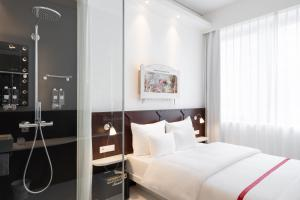 A bed or beds in a room at Ruby Leni Hotel Dusseldorf