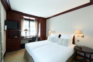 سرير أو أسرّة في غرفة في وارويك بروكسل - قصر غراند