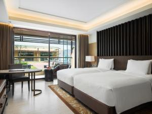 A bed or beds in a room at JW Marriott Mussoorie Walnut Grove Resort & Spa