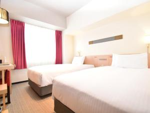 A bed or beds in a room at ibis Styles Kyoto Station