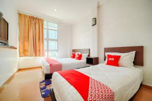 A bed or beds in a room at OYO 89765 Motel Arau