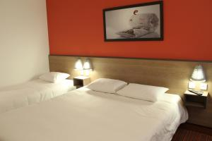 A bed or beds in a room at Ace Hotel Chateauroux