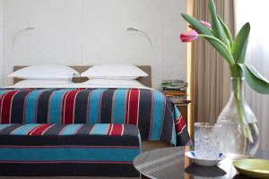 A bed or beds in a room at Mendeli Street Hotel