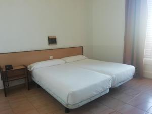 A bed or beds in a room at Hotel Monegal
