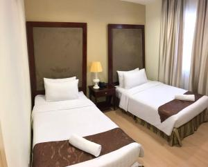 A bed or beds in a room at The Capital Residence Suites