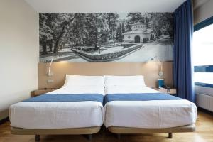 A bed or beds in a room at Aparthotel Campus