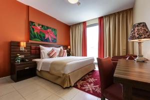 A bed or beds in a room at Abidos Hotel Apartment Al Barsha