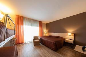 A bed or beds in a room at Hotel Donatello Imola