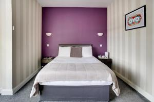 A bed or beds in a room at OYO Gin House Hotel