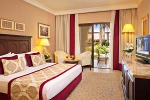 سرير أو أسرّة في غرفة في فندق ومنتجع ميرامار شاطئ العقة