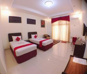 A bed or beds in a room at VIP Hotel Cianjur
