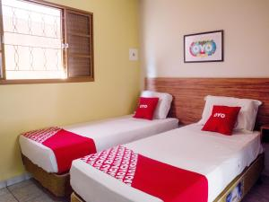 A bed or beds in a room at OYO Athenas Apart Hotel