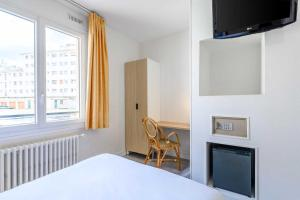 A television and/or entertainment center at Comfort Hotel Rouen Alba