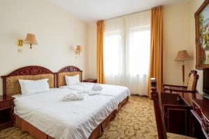 A bed or beds in a room at Hotel Bellevue Esztergom