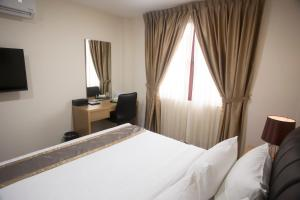 A bed or beds in a room at Al Afiah Hotel