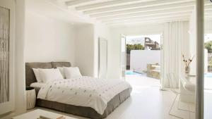 A bed or beds in a room at Cavo Tagoo Mykonos