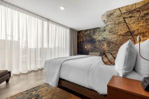 A bed or beds in a room at Cambria Hotel Omaha Downtown