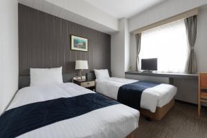 Tempat tidur dalam kamar di Tottori City Hotel