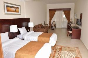 A bed or beds in a room at Akas-Inn Hotel Apartment