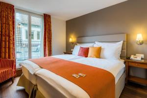 Ein Bett oder Betten in einem Zimmer der Unterkunft Hotel Des Alpes