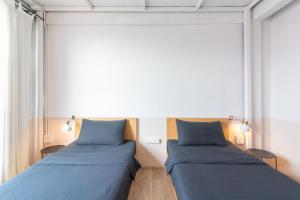 A bed or beds in a room at Beige Poshtels + Netflix