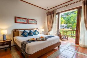 A bed or beds in a room at Riverside Boutique Resort, Vang Vieng