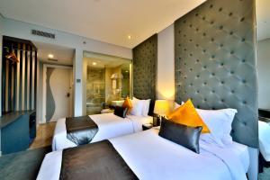 Tempat tidur dalam kamar di Serela Cihampelas by KAGUM Hotels
